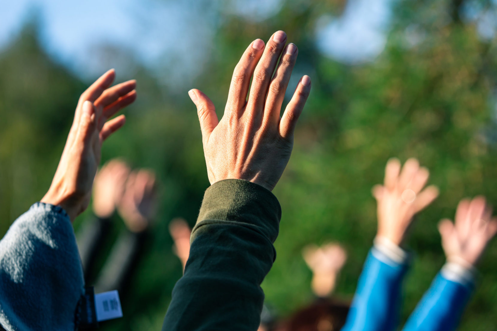 Group of people putting their hands up in the air.