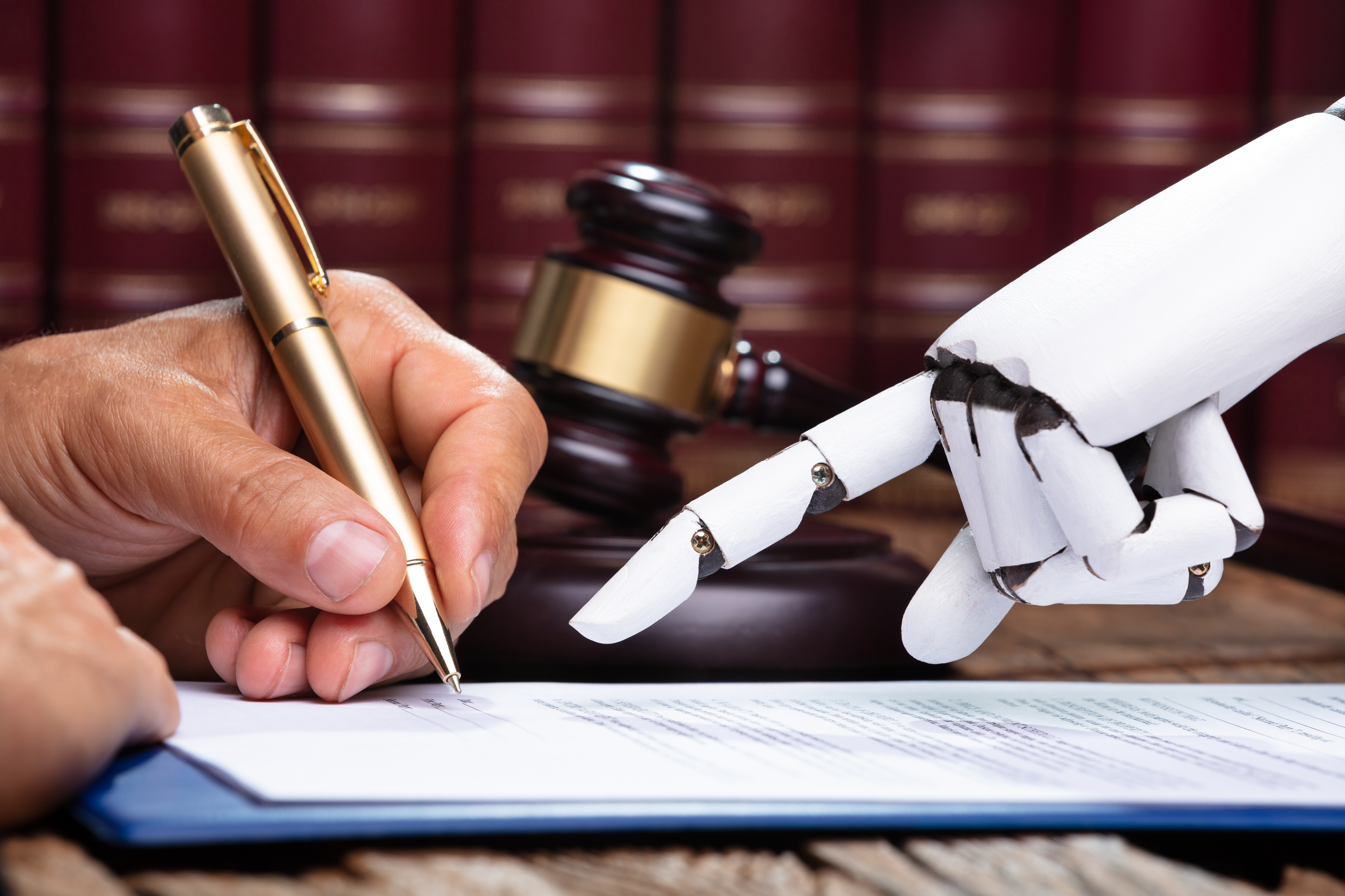 A robot hand helps a human hand sign a law document.